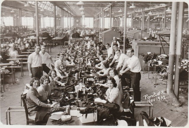 """This photo of women at their sewing machines was taken in 1932, long after the labor movement began. Notice the improvements in working conditions, such as windows and handsome """"massage men."""""""